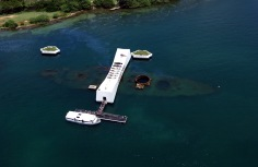 An aerial view of the USS Arizona Memorial with a US Navy (USN) Tour Boat, USS Arizona Memorial Detachment, moored at the pier as visitor disembark to visit and pay their respects to the Sailors and Marines who lost their lives during the attack on Pearl Harbor on December 7, 1941.